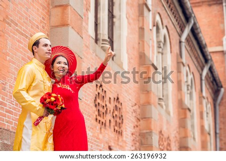 Beautiful bride in Vietnamese national costume showing something to her husband