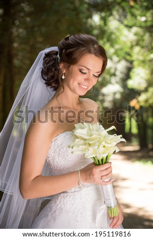 Beautiful bride in wedding dress and bridal bouquet, happy newlywed woman with wedding flowers, woman with wedding makeup and hairstyle. gorgeous young bride outdoors. Bride waiting for groom. bride - stock photo