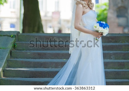 Beautiful bride in wedding dress with bouquet - stock photo