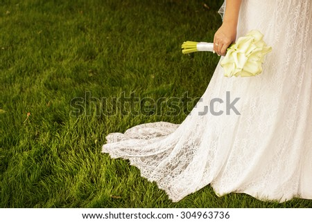 Beautiful Bride in White Wedding Dress Holding Bouquet of White Calla Lilies. Green Grass Meadow Background - stock photo