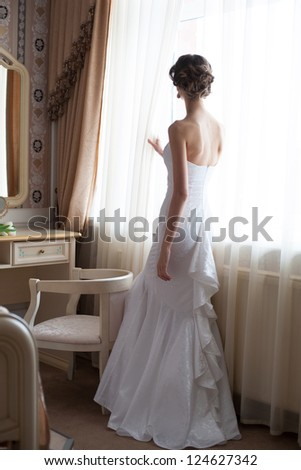 Beautiful bride in white wedding dress standing in her bedroom and looking in window - stock photo