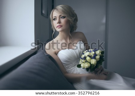 Beautiful bride in white wedding dress with bridal bouquet, with yellow and blue flowers - stock photo