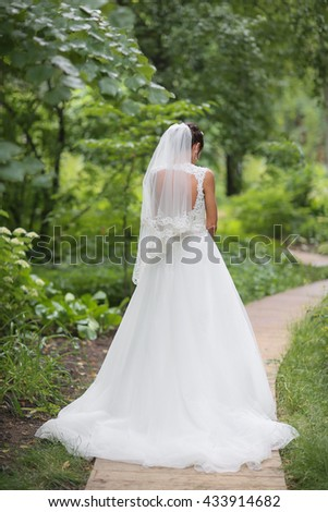 beautiful bride is standing in wedding dress on green background, view from behind