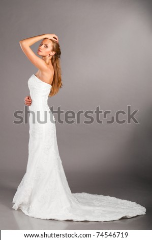 beautiful bride is standing in wedding dress on grey background, side view - stock photo