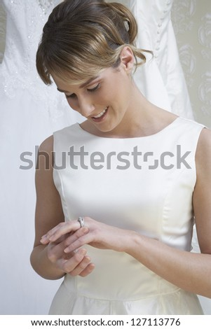 Beautiful bride looking at her wedding ring and smiling