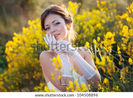 Beautiful bride outdoor portrait in yellow flowers