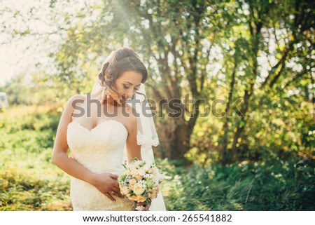 Beautiful bride outdoors in a forest - stock photo