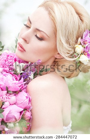 Beautiful bride outdoors in a green flowers with peony bouquet. Tenderness blond. - stock photo