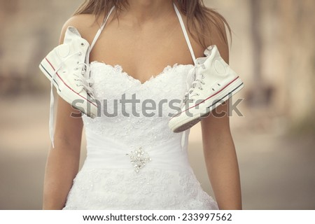 Beautiful bride outdoors , wedding sneakers (cross processing) - stock photo