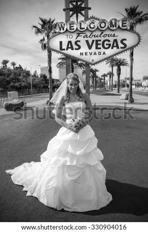 Beautiful bride poses at the las vegas sign - stock photo
