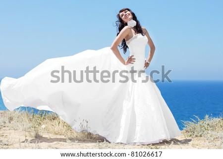Beautiful bride posing at sea coast - stock photo