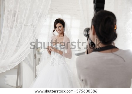 Beautiful bride posing front of photographer in white interior. - stock photo