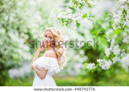 Beautiful bride posing near apple-tree in blossom - stock photo