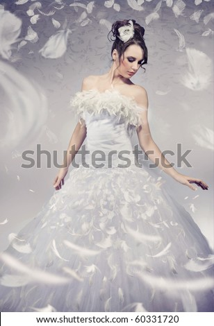 Beautiful bride posing over white flying feathers - stock photo