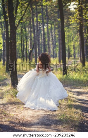 Beautiful bride run outdoors in a forest.