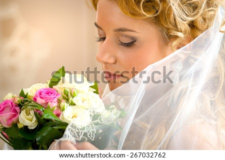 Beautiful bride smelling a wedding bouquet