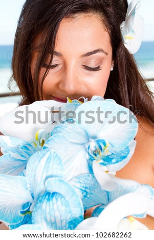 beautiful bride smelling bouquet - stock photo