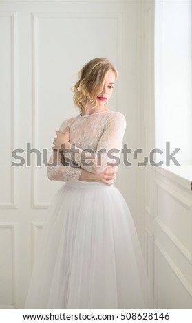 Beautiful bride standing at window in white room.