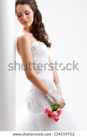 beautiful bride standing back to the  white column with closed eyes, studio shot