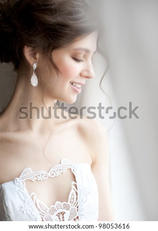 Beautiful bride standing near the window and smiling - stock photo