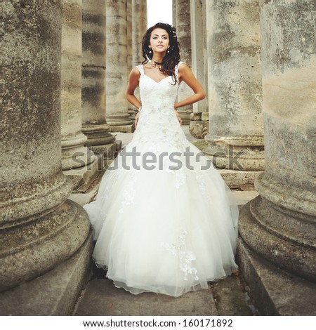 beautiful bride stands between the columns - stock photo