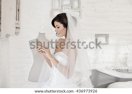 Beautiful bride using mobilephone, side view.