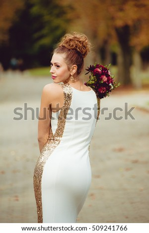 Beautiful bride walking in the park with wedding bouquet before wedding ceremony in church