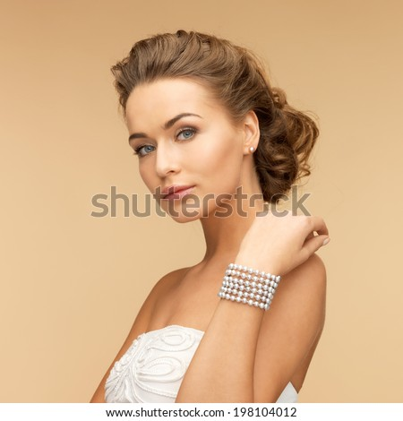 beautiful bride wearing pearl earrings and bracelet - stock photo