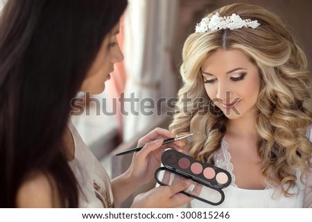 Beautiful bride wedding with makeup and hairstyle. Stylist makes make-up bride on wedding day. portrait of young woman at morning. - stock photo