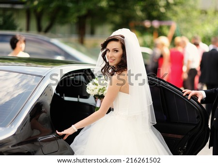 Beautiful bride with bouquet of flowers in the car  - stock photo
