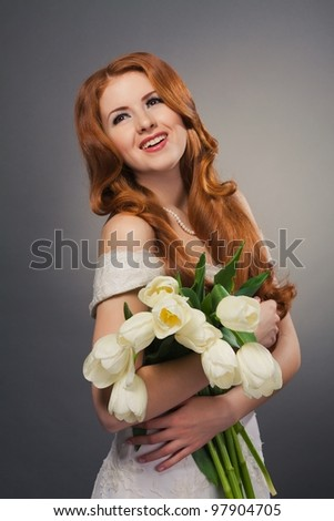 beautiful bride with curly red hair in wedding dress with flowers