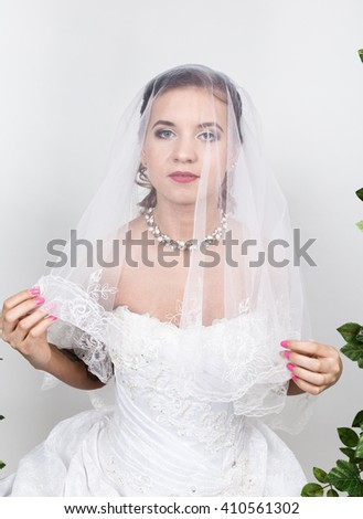 Beautiful bride with fashion wedding hairstyle. Close-up portrait of young gorgeous bride. Wedding, girl's face is hidden veil - stock photo