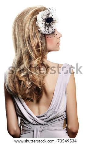 beautiful bride with long blond hair in big hairstyle, wearing flower headband with veil over her face and an open back gray dress on white background. - stock photo