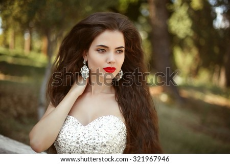 Beautiful bride with long wavy hair and fashion earrings, posing in wedding dress, outdoors portrait in park