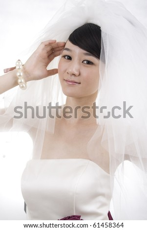 Beautiful bride with perfect natural makeup,smiling,wearing mantilla,pearls round wrist - stock photo