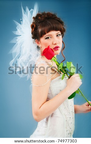 Beautiful bride with rose in studio shooting - stock photo