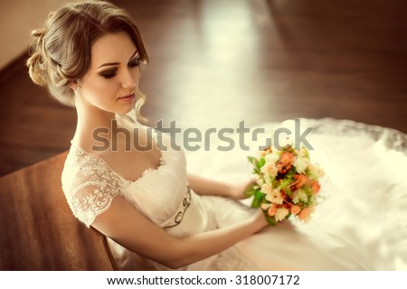 Beautiful bride with stylish make-up in white dress - stock photo