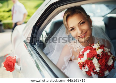 Beautiful bride with the bouquet in the wedding car - stock photo