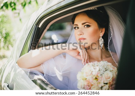 Beautiful bride with wedding bouquet in a car. Wedding day - stock photo