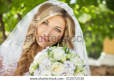 Beautiful bride with wedding bouquet of flowers outdoors in green park. - stock photo