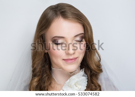 Beautiful bride woman girl lady princess prepare for wedding, white long veil, silk flower necklace. Professional make up bright eyes, tender pink lipstick, long light wavy hair. background free place