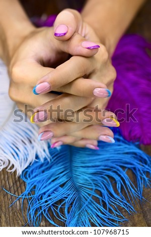 Beautiful bright colored manicure on a background of feathers