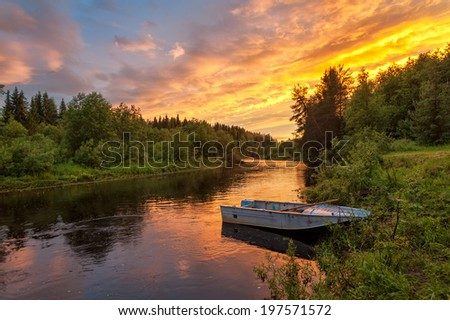 Beautiful bright dramatic sunset over river with forest along riverside and boat in foreground. Arkhangelsky region, Russia.