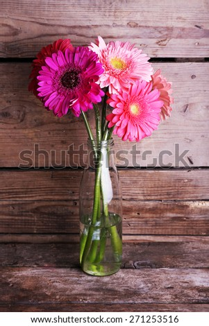 Beautiful bright gerbera flowers in glass vase on wooden background - stock photo