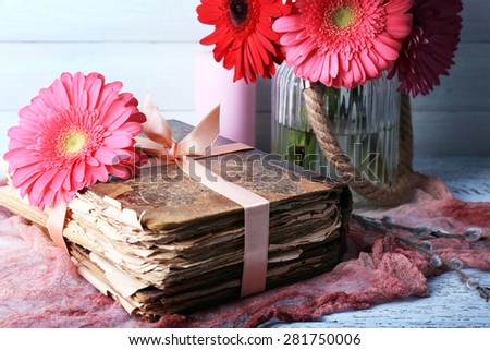 Beautiful bright gerberas in vase with old books on table close up - stock photo