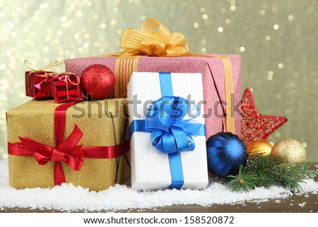 Beautiful bright gifts and christmas decor, on shiny background - stock photo