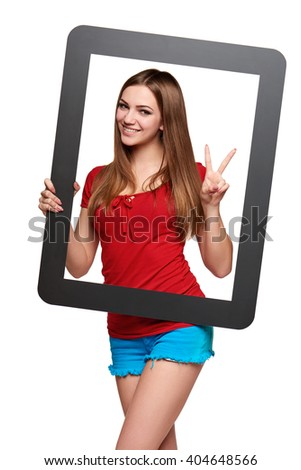 Beautiful bright girl standing looking through the frame and gesturing V sign, over white background - stock photo
