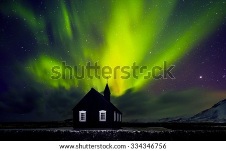 Beautiful bright green Northern light over church, little village in the Iceland, amazing forces of nature, wonderful night sky landscape  - stock photo