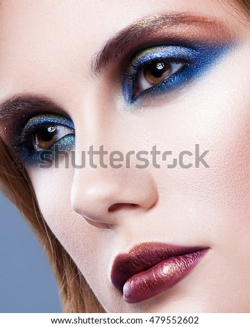 Beautiful bright makeup with blue eyeshadow. Short hair style. Closeup