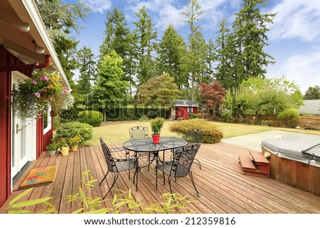 Beautiful bright red house with patio area on walkout deck and small red shed on backyard